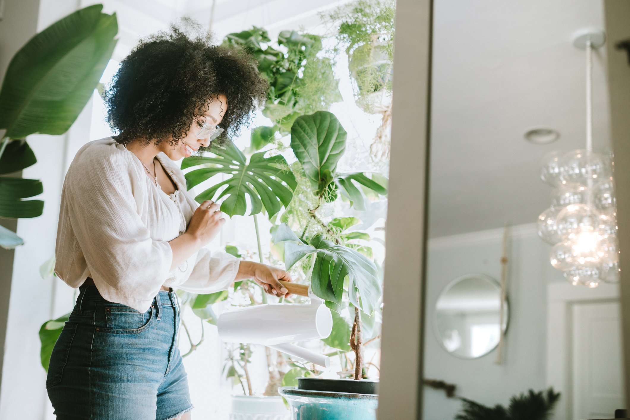 Young woman waters her house plants