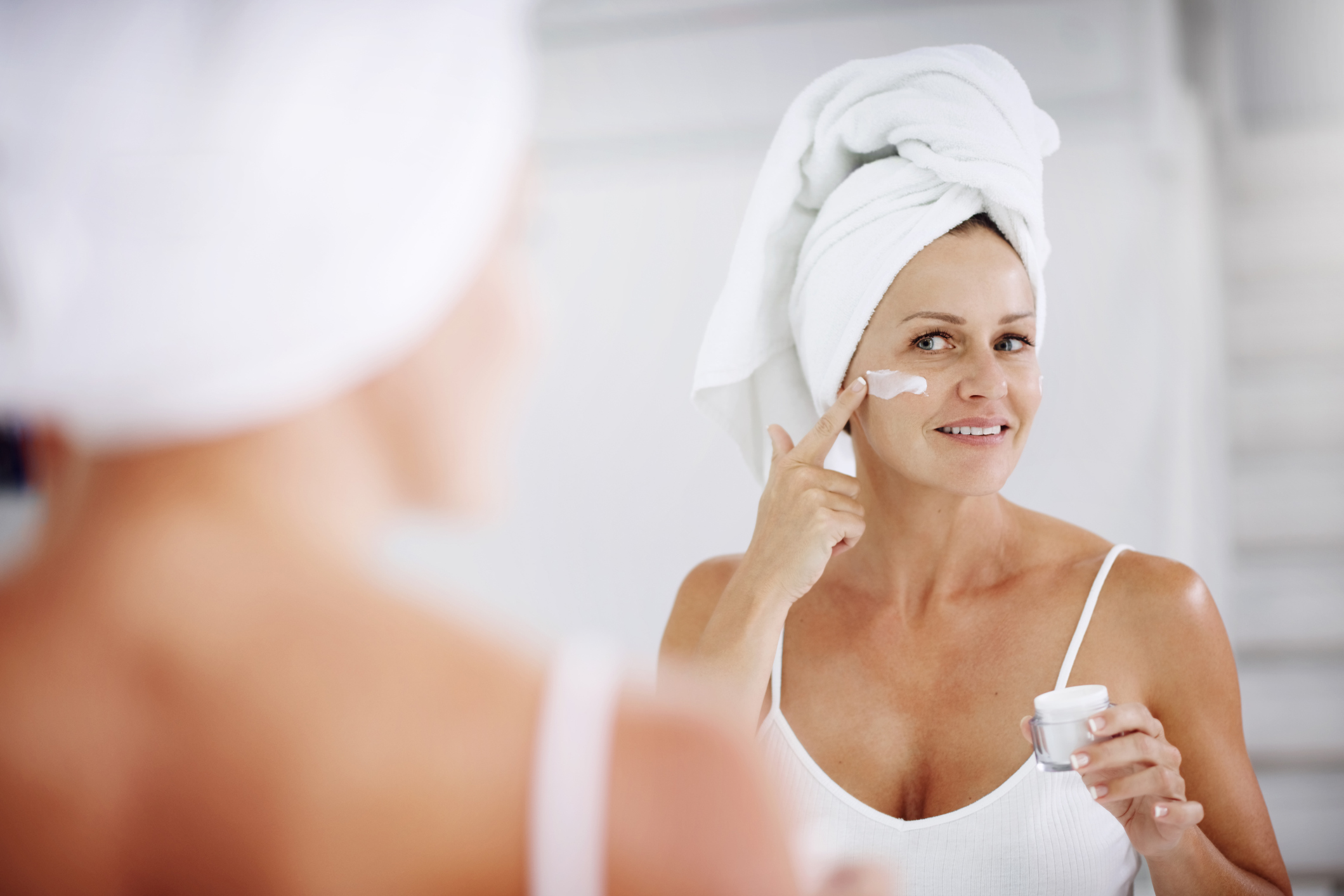 Older woman applies skin cream in the mirror