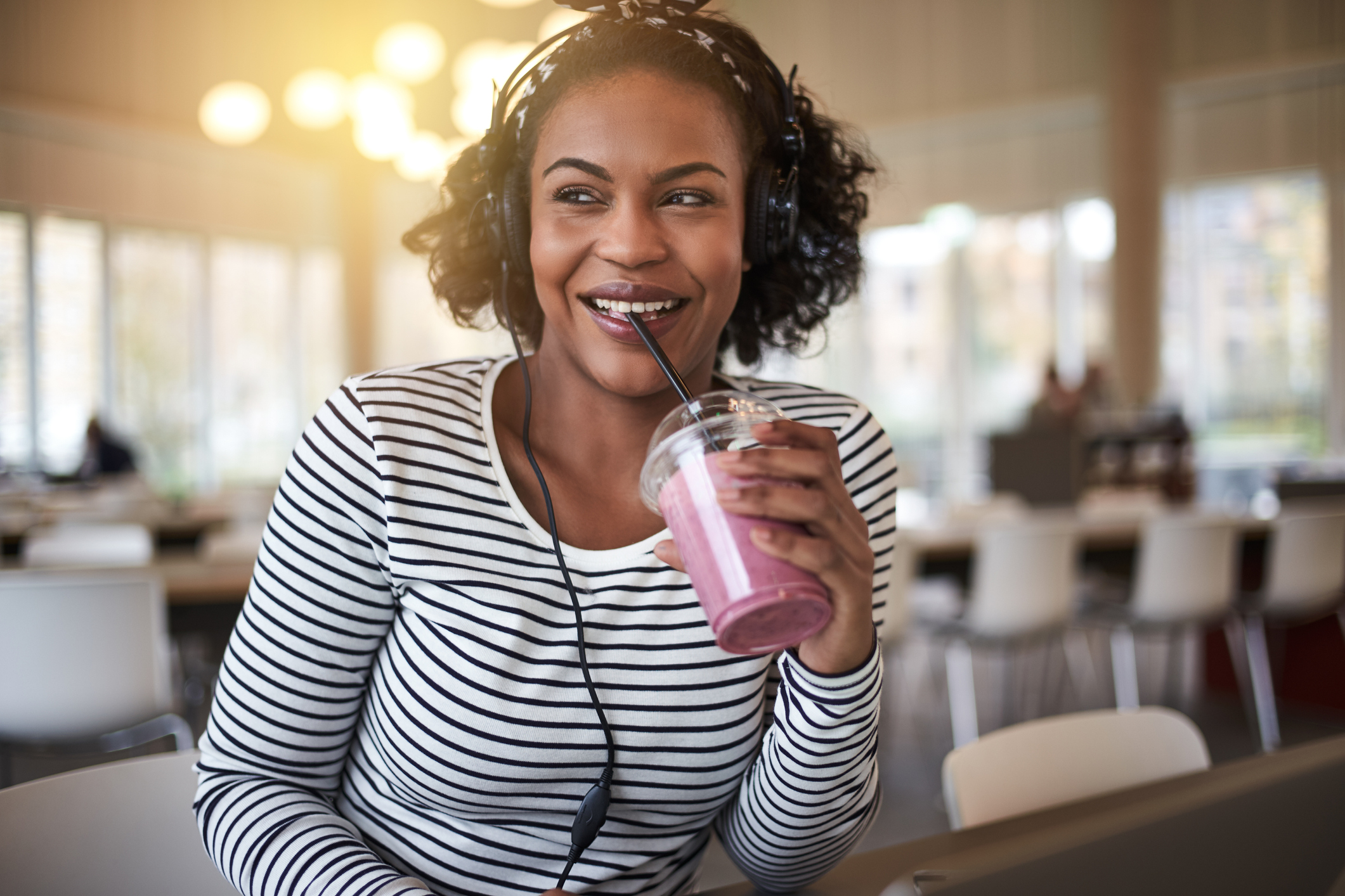 Smiling young college student drinking a smoothie between classes