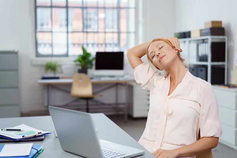 Tired young businesswoman taking a break and a moment to relax with her eyes closed and head tilted to the side