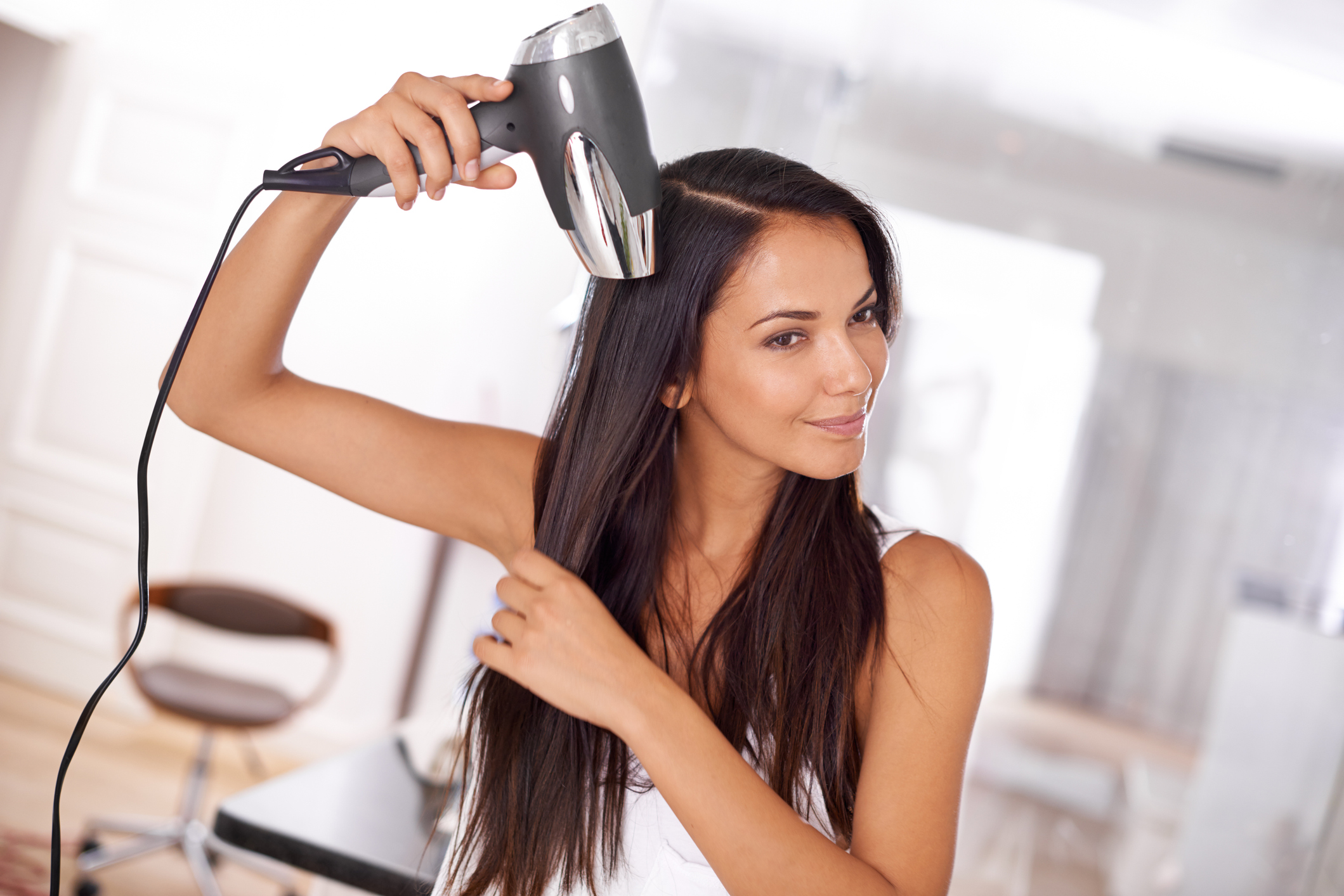 Woman blow dries her long straight hair