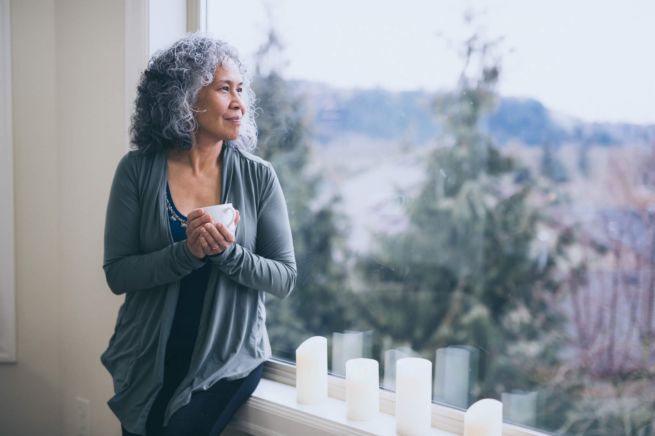 Beautiful mature woman stands by her window in the early morning with a cup of tea