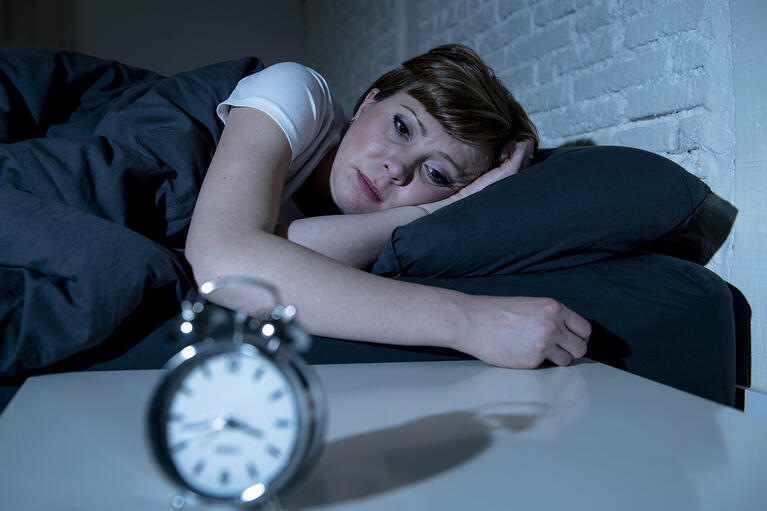 A woman in bed with anxiety