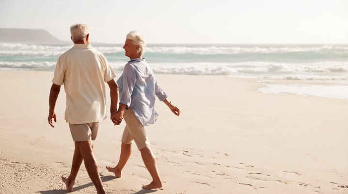 rear-view-of-senior-couple-walking-along-beach-hand-in-hand-picture-id939174234