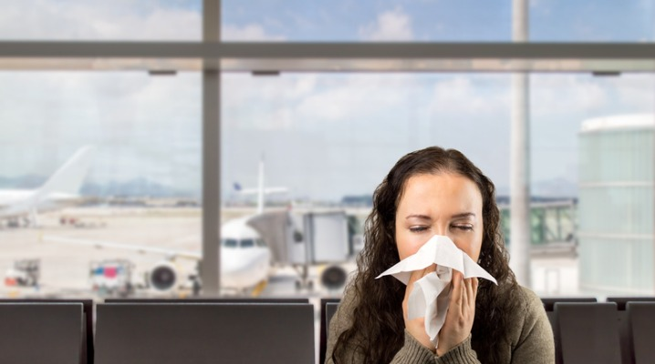 sick-woman-sneezing-at-the-airport-picture-id486655506